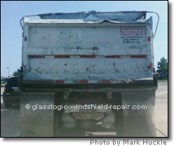 truck with damaged tarp and gravel falling out on the road